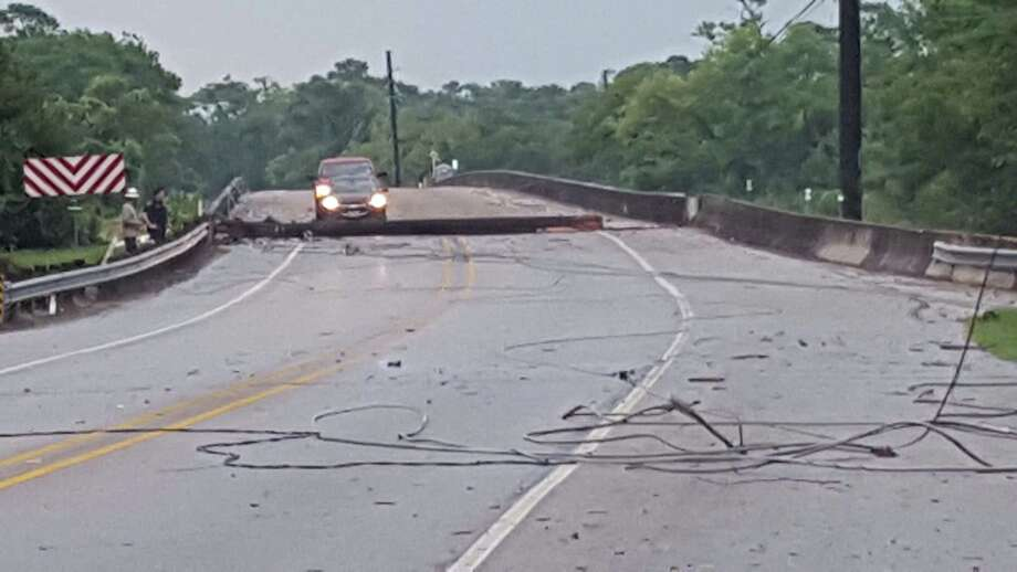 A sudden microburst Friday afternoon shortly after 5 p.m. snapped a light pole that fell across a bridge in the 19500 block of Old Beaumont Highway in northeast Harris County trapping two vehicles. Photo: David Taylor / Staff Photo