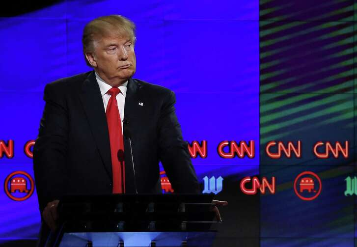 In this file photo taken on March 10, 2016 Donald Trump listens to Texas Sen. Ted Cruz (not pictured) speak during the CNN Republican Presidential Debate in Miami, Fla.