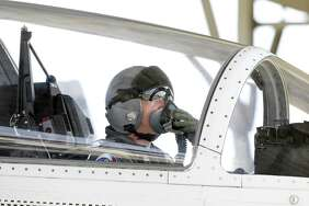 A pilot adjusts his oxygen mask as his crew prepares to fly T-6A aircraft at Joint Base San Antonio-Randolph on March 2, 2018.