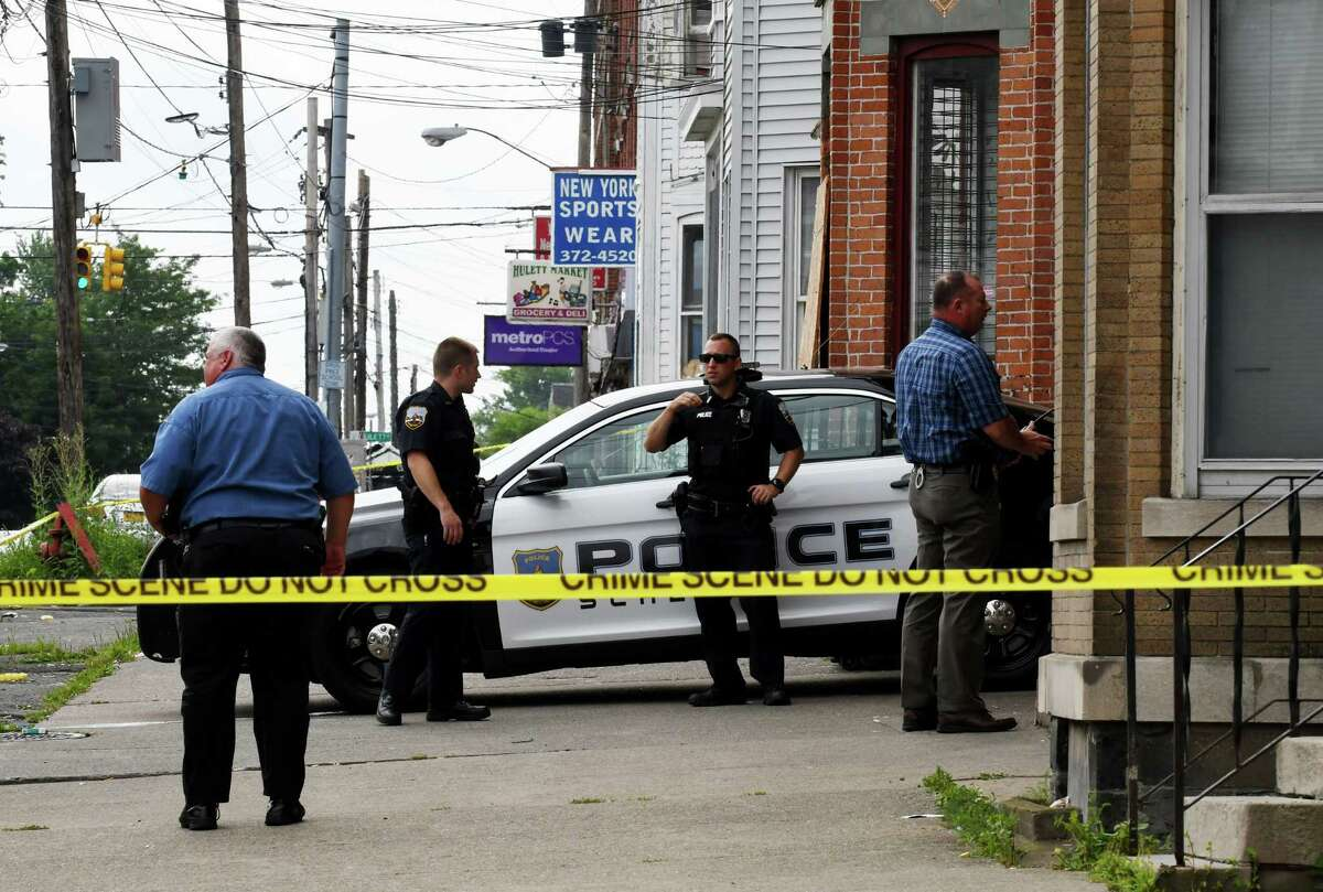 Police remain on the scene at 766 State St. on Friday, Aug. 10, 2018, in Schenectady, N.Y. A child's body was found in the backyard of the apartment building when police searched the property on Thursday evening. (Will Waldron/Times Union)