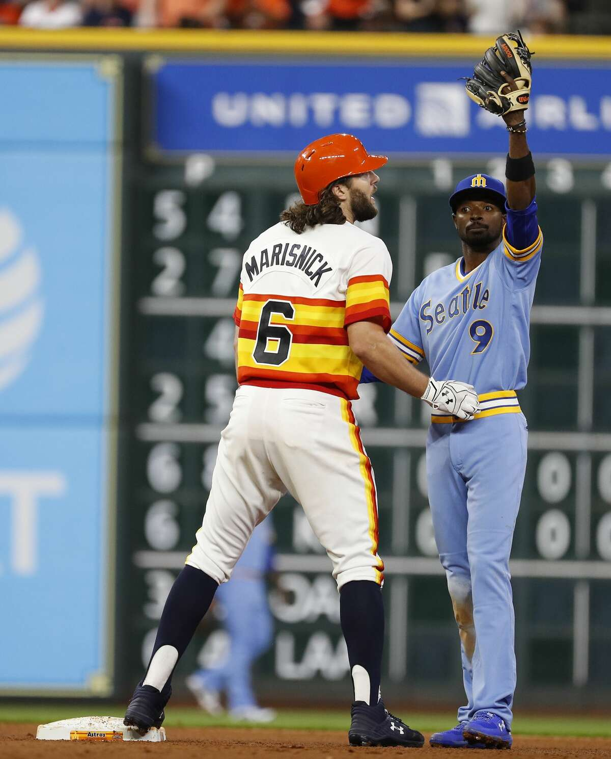 Seattle Mariners Dee Gordon (9) signals for a trainer for Houston Astros Jake Marisnick (6) who was injured after hitting a double during the seventh inning of an MLB game at Minute Maid Park, Friday, August 10, 2018, in Houston.