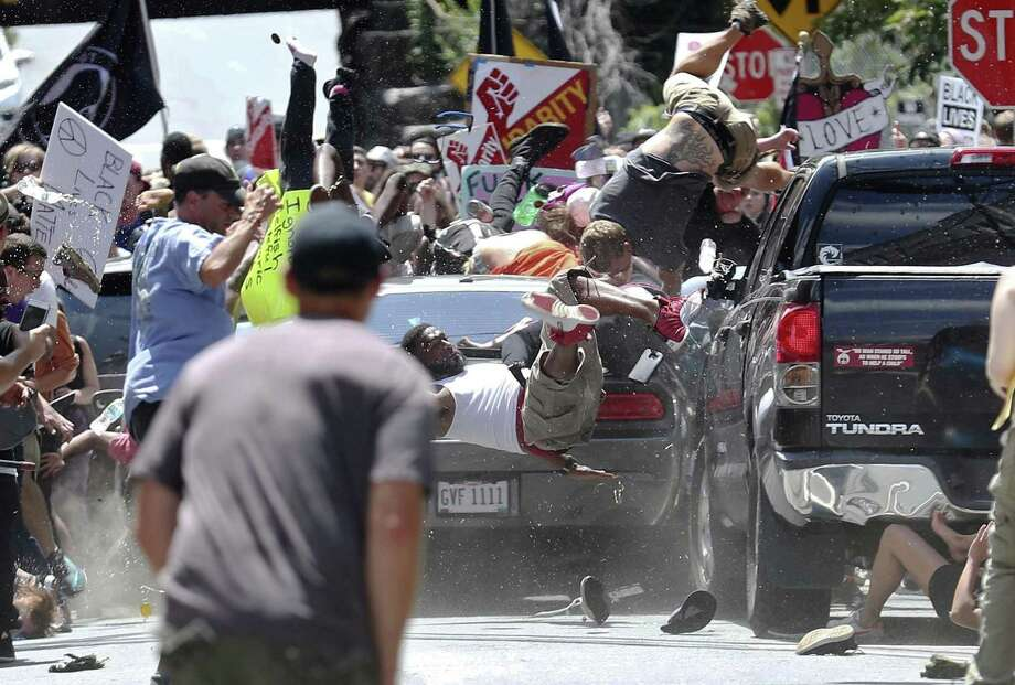 People fly into the air as a vehicle drives into a group of protesters demonstrating against a white nationalist rally Aug. 12, 2017, in Charlottesville, Va. Efforts to take down America's monuments honoring slain Confederate soldiers and the generals who led them gained explosive momentum following the deadly violence a year ago in Charlottesville.  Photo: Ryan M. Kelly, MBO / Associated Press / The Daily Progress