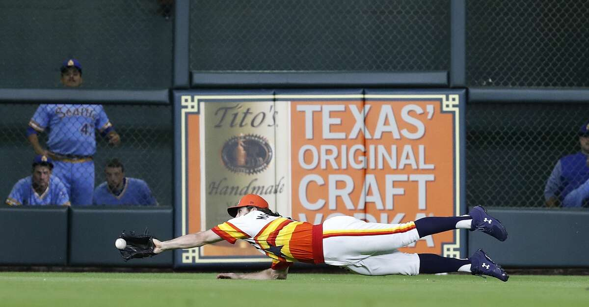 Houston Astros Jake Marisnick (6) dives to catch Seattle Mariners Kyle Seager's line out during the sixth inning of an MLB game at Minute Maid Park, Friday, August 10, 2018, in Houston.