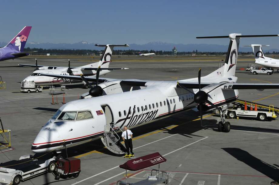 pilot at the airstairs of an Horizon Air Bombardier DHC-8 Dash 8-400 Q400 parked on the apron with tug attached, baggage conveyor-belt truck, a DHC-8 Dash 8-200 and tail-fin of an Hawaiian Airlines Boeing 767-300 behind. (Photo by: aviation-images.com/UIG via Getty Images) Photo: Aviation-images.com/UIG Via Getty Images