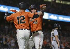 San Francisco Giants' Derek Holland (45) is greeted by teammate Joe Panik, left, after they scored in the third inning of a baseball game against the Pittsburgh Pirates on Friday, Aug. 10, 2018, in San Francisco. The pair scored after the Giants' Buster Posey singled to center field. At right is Pirates catcher Francisco Cervelli. (AP Photo/Eric Risberg)
