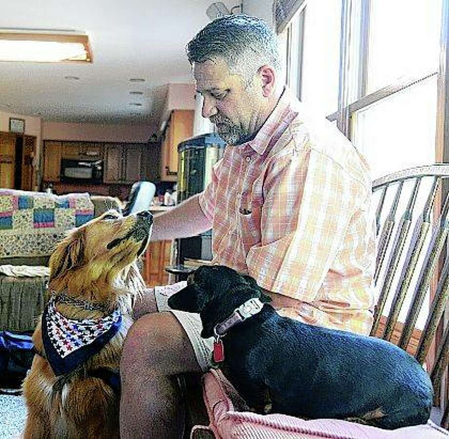 King of Glory Lutheran parishioner Matthew Ponsolle pets the congregation's new comfort dog, Julia, in South Elgin. The dog is from the same ministry run by Lutheran Church Charities that brings dogs to disaster sites, such as school shootings or tornadoes. Julia lives with Ponsolle and his family. Photo:       Rick West | Daily Herald (AP)