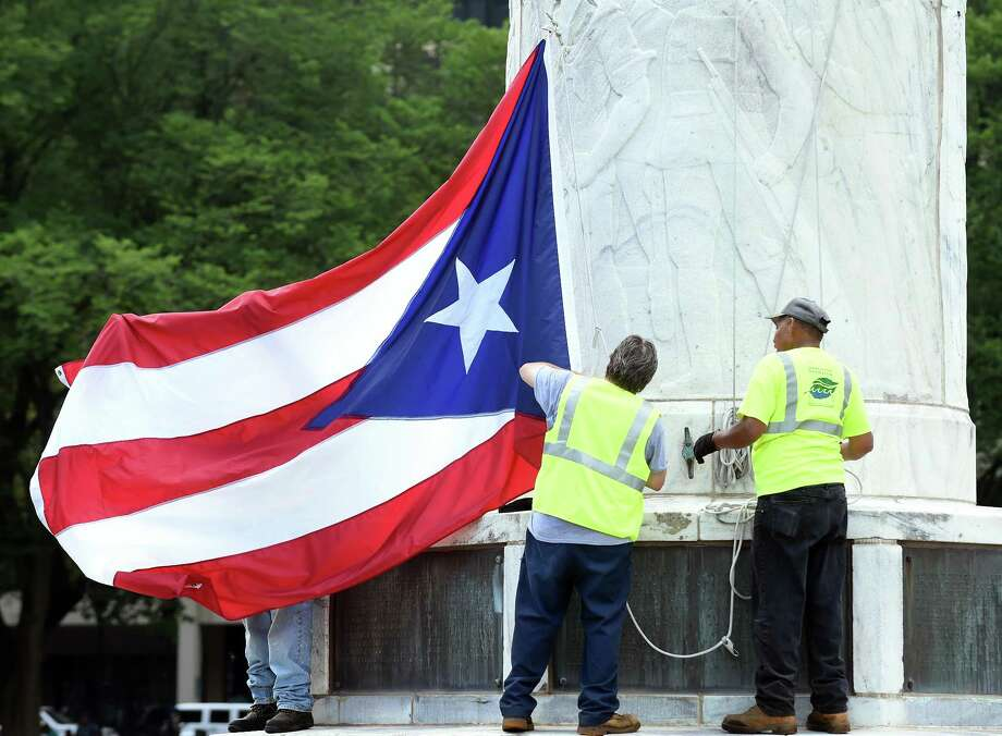 New Haven Parks, Recreation and Trees employees prepare the Puerto Rican flag to be raised on the New Haven Green in honor of the Third Annual New Haven Puerto Rican Festival. Due to inclement weather, the festival will be held indoors Saturday. Photo: Arnold Gold / Hearst Connecticut Media / New Haven Register