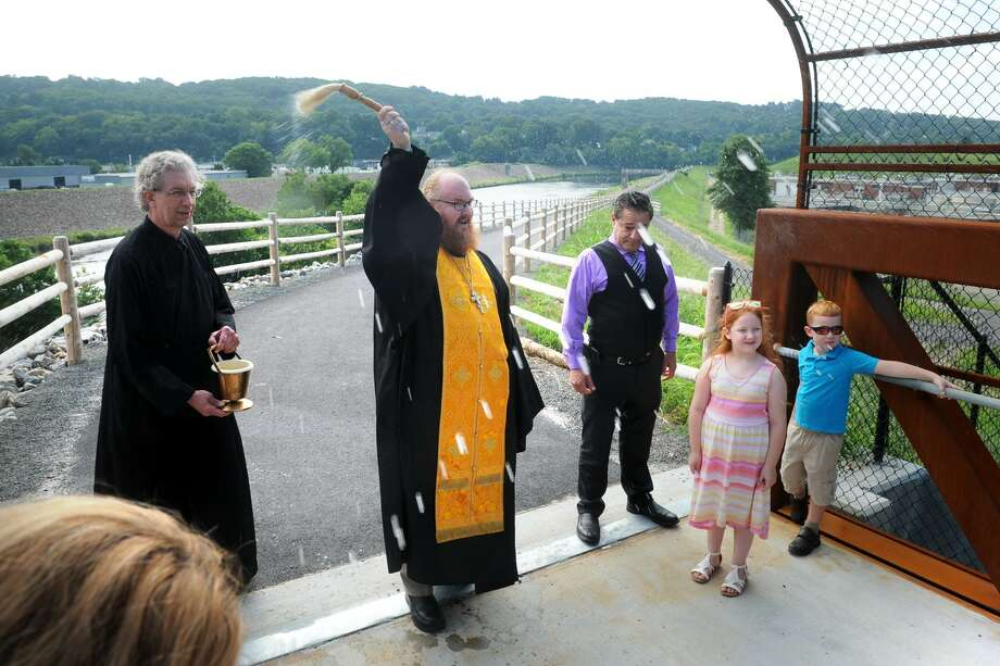 Rev. Patrick Burns from Three Saints Orthodox Church, in Ansonia, is joined by others as he blesses the pedestrian bridge leading to the newly completed section of Ansonia Riverwalk Park, in Ansonia, Conn. Aug. 8, 2018. The bridge spans the rail tracks next to Pershing Drive, and now connects the Naugatuck River Greenway to pedestrian and bicycle traffic south through Ansonia, Derby and Shelton. Photo: Ned Gerard / Hearst Connecticut Media / Connecticut Post