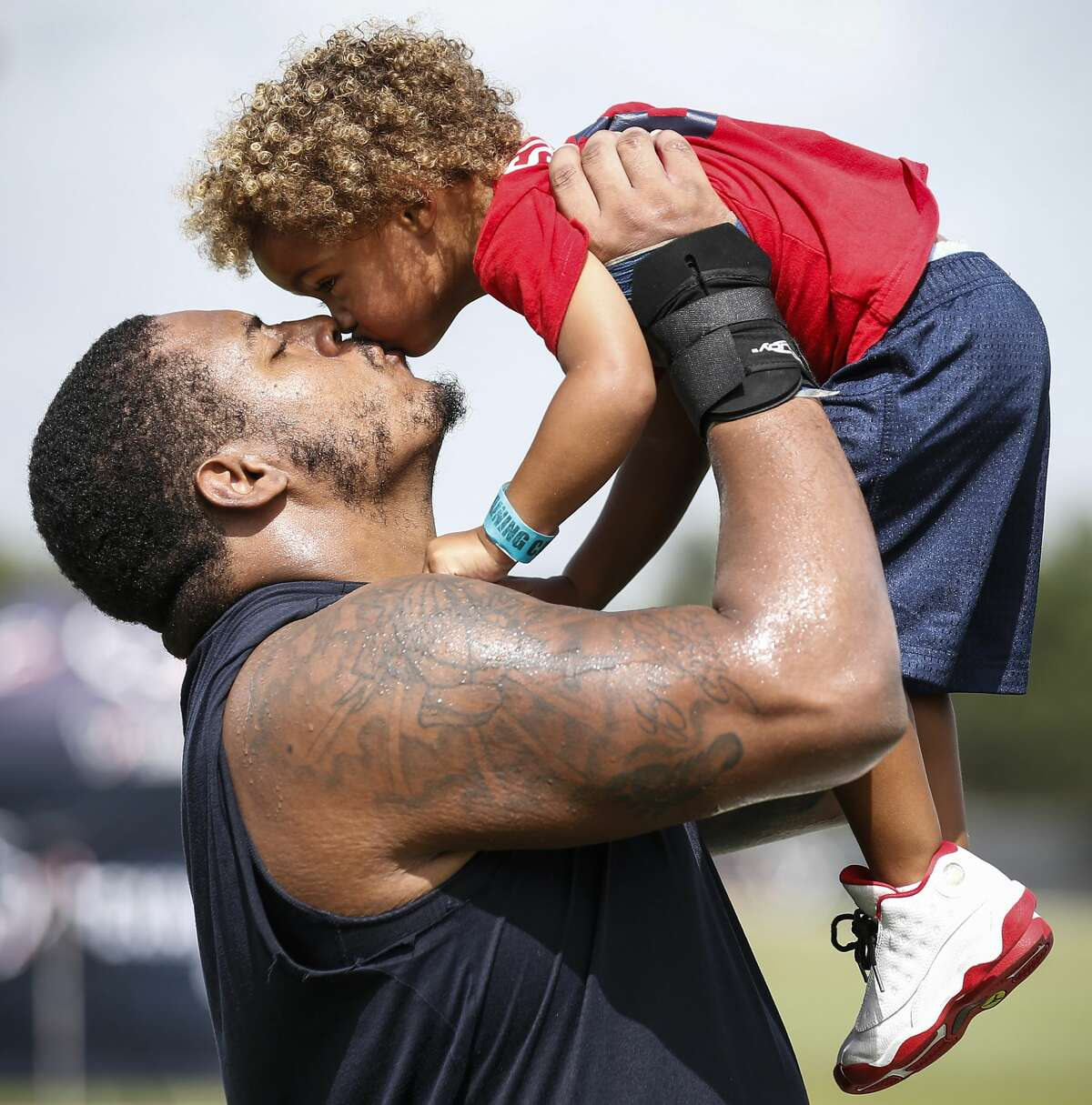 Houston Texans offensive guard Chad Slade lifts his son, Braxton, and gives him a kiss following practice during training camp at the Methodist Training Center on Saturday, Aug. 11, 2018, in Houston.