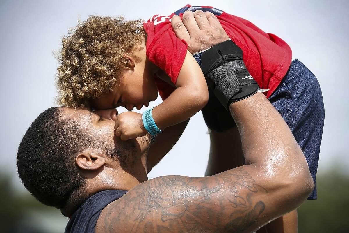 Houston Texans offensive guard Chad Slade lifts his son, Braxton, up and embraces the 2-year-old following practice during training camp at the Methodist Training Center on Saturday, Aug. 11, 2018, in Houston.