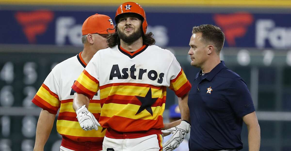 Assistant trainer Scott Barringer assists Jake Marisnick (6) who was injured after hitting a double during the seventh inning of an MLB game at Minute Maid Park, Friday, August 10, 2018, in Houston.