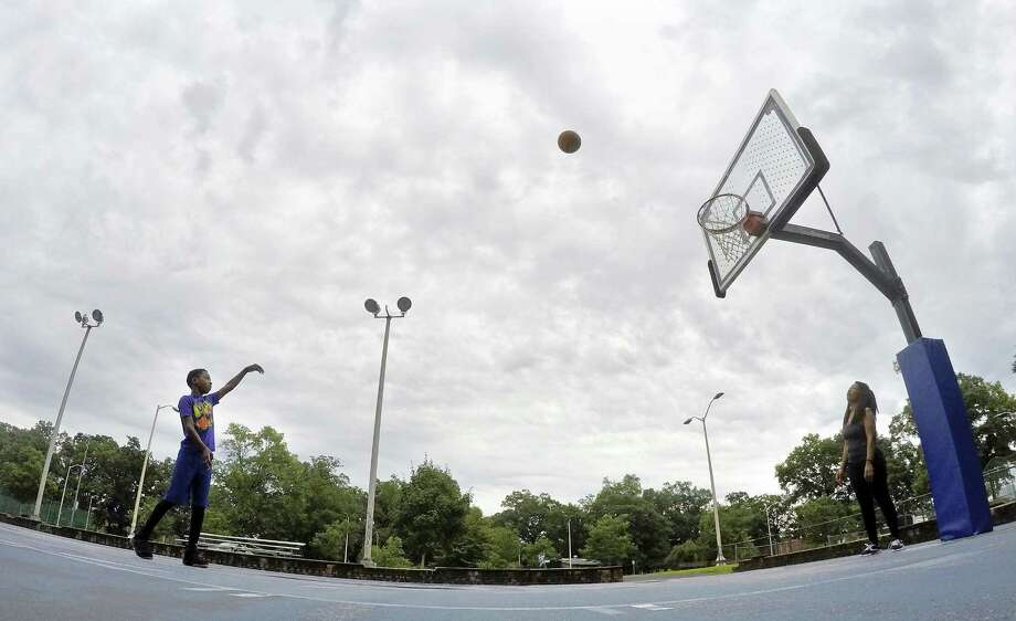 Eleven year-old Joseph Parker of Stamford doesn't let the foul weather get in his way of hoop time at the Scalzi Park courts on August 11, 2018 in Stamford, Connecticut. Parker was practicing his jump shots with his mother Renée Prosper.  The National Weather Service has issued a flash flood watch Saturday and into Sunday for portions of southern Connecticut, including Fairfield, Middlesex, New Haven and New London counties. Showers, thunderstorms and possible heavy rain are expected Saturday and into Saturday night. Photo: Matthew Brown / Hearst Connecticut Media / Stamford Advocate