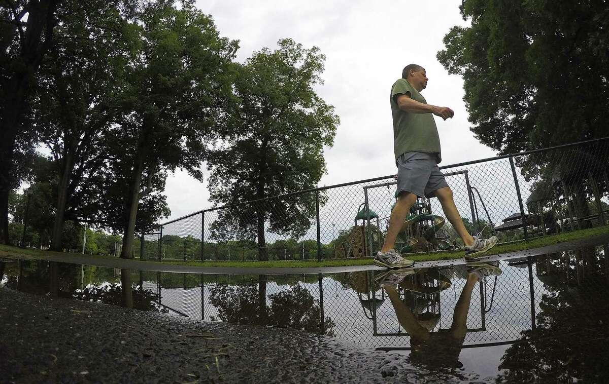 A walker is reflected in a puddle at Scalzi Park following a light rain fall on August 11, 2018 in Stamford, Connecticut.