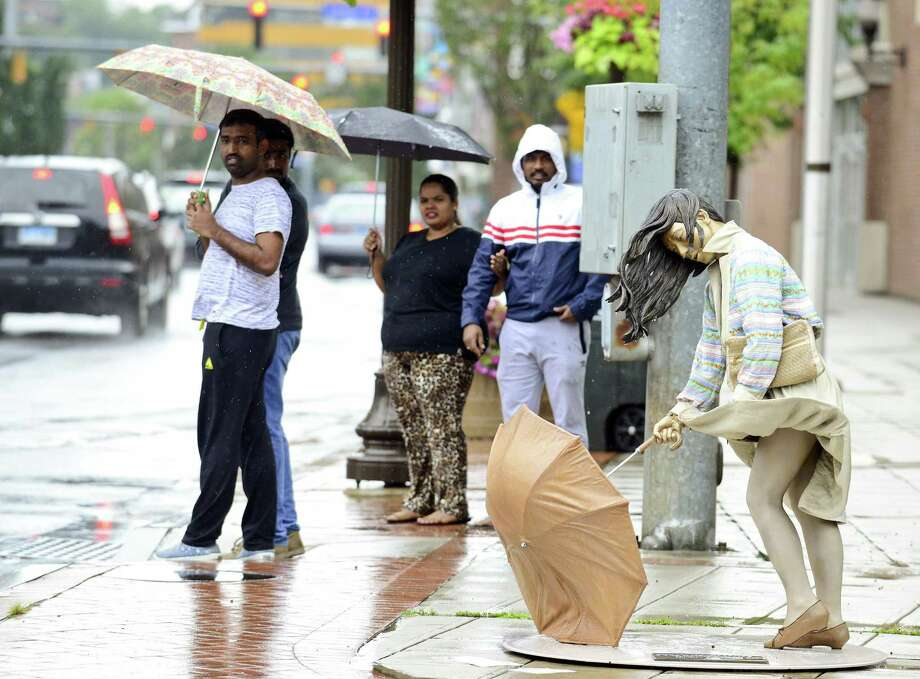 "Pedestrians clad umbrella's shielding themselves during a light rain fall, oblivious to the struggles of ""Stormy Weather"" one of several statues by Seward Johnson that are displayed throughout Stamford's Downtown business district on August 11, 2018 in Stamford, Connecticut. Photo: Matthew Brown / Hearst Connecticut Media / Stamford Advocate"