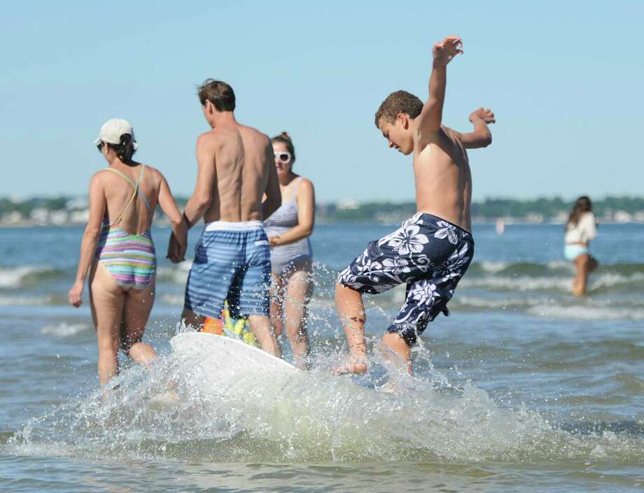 Aidan Pray, 14, of Valhalla, N.Y., skimboards on the beach before the Independence Day fireworks at Greenwich Point Park in Old Greenwich, Conn. Saturday, July 7, 2018. Photo: Tyler Sizemore / Hearst Connecticut Media / Greenwich Time