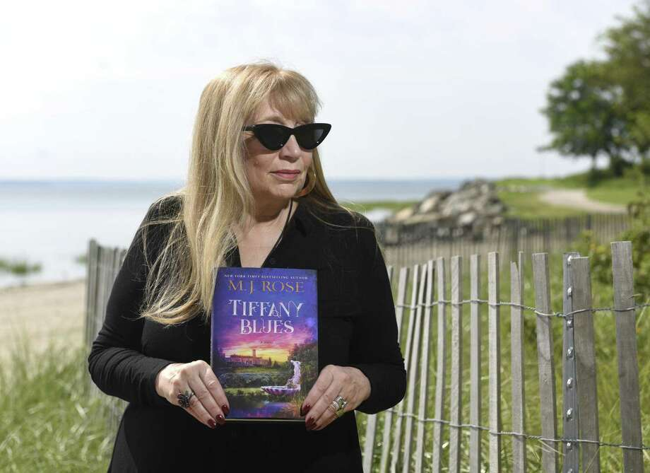 "Local author M.J. Rose poses with her new book ""Tiffany Blues"" at Greenwich Point Park in Old Greenwich, Conn. Thursday, Aug. 9, 2018. In ""Tiffany Blues,"" Rose crafts a historical novel around a prestigious summer artists' colony run by Louis Comfort Tiffany, of Tiffany & Co., at the infamous Laurelton Hall estate. Photo: Tyler Sizemore / Hearst Connecticut Media / Greenwich Time"