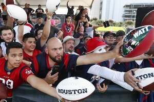 Houston Texans fans reach out seeking autographs following practice during training camp at the Methodist Training Center on Saturday, Aug. 11, 2018, in Houston.