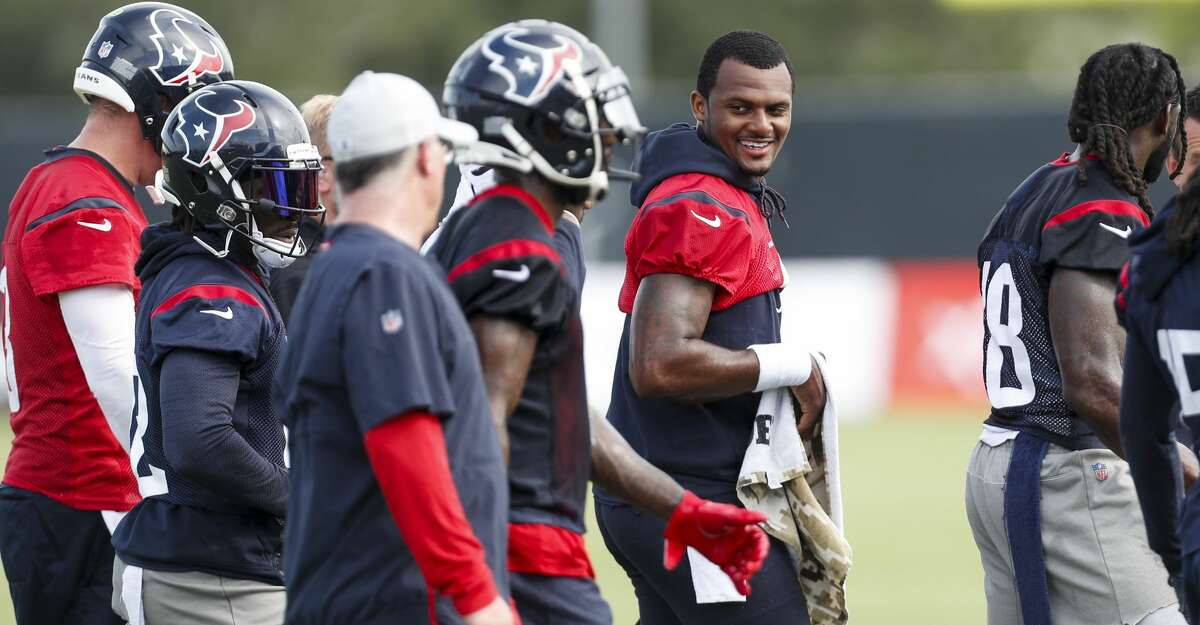 Houston Texans quarterback Deshaun Watson, right, smiles as he walks off the field with his teammates during training camp at the Methodist Training Center on Saturday, Aug. 11, 2018, in Houston.