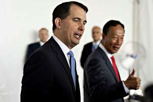 Scott Walker, governor of Wisconsin, left, walks with Terry Gou, chairman of Foxconn Technology Group, right, ahead of a groundbreaking ceremony for the Foxconn facility in Mount Pleasant, Wisconsin, U.S., on Thursday, June 28, 2018. After repeatedly bashing the leadership of an iconic American manufacturer this week, Trump was 30 miles away from its Wisconsin headquarters to praise a Taiwanese company for bringing jobs to a state critical to his re-election. Photographer: Daniel Acker/Bloomberg