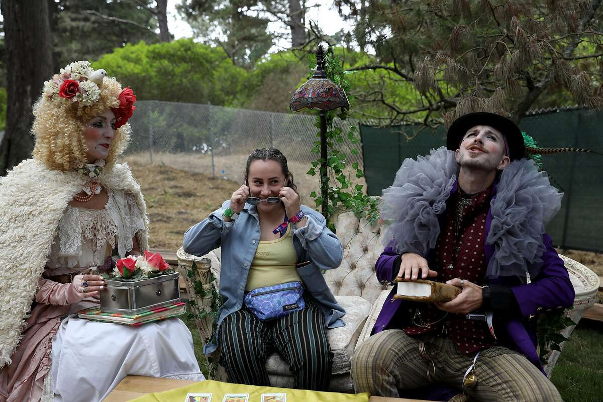 Christiane Georgi as Mademoiselle Ladida and Rebecca Weston look at Noah Lance as Billy Baffle as he takes a seat in the Grand Artique area at Outside Lands at Golden Gate Park in San Francisco, Calif., on Friday, August 10, 2018. Georgi and Lance are performers with Grand Artique, based in San Diego.