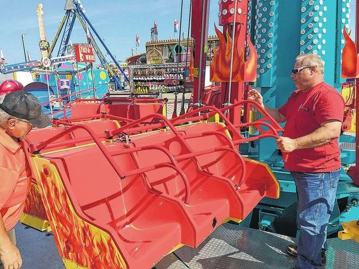 """FILE - Illinois Department of Labor amusement ride safety inspectors Bill Szerletich, left, and Brian Brown inspect the safety bars on the compartments of the carnival ride """"Downdraft,"""" a ride in the midway of the Illinois State Fair in Springfield."""