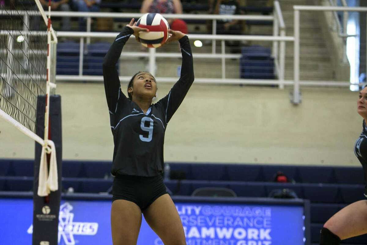 Jevani Hanspard sets Amaia Martin during Harlan's varsity volleyball team's first game at Paul Taylor Fieldhouse Aug. 7, 2018.