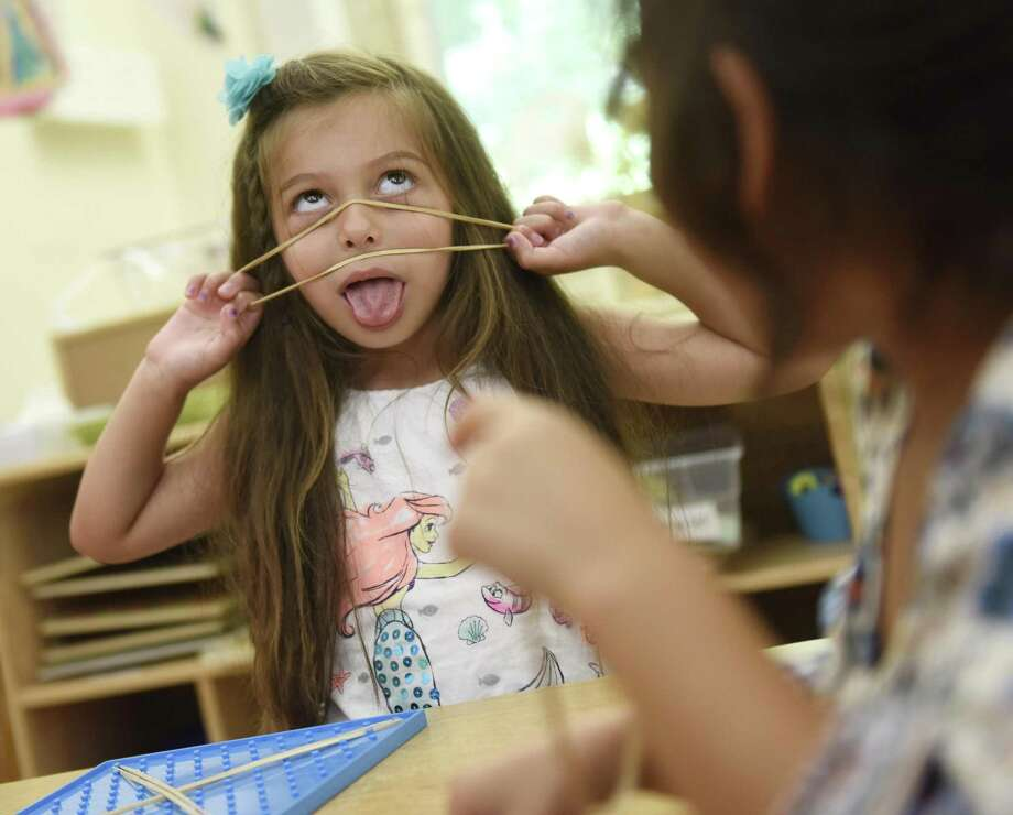 d483cf7c89c2 Rising kindergartener Bella Quesada makes a funny face with a rubber band  during playtime at Gateway