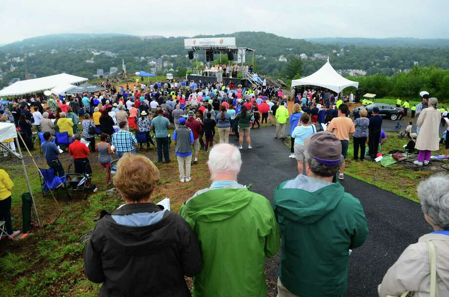 Hundreds of people attend a Mountaintop Mass held at Holy Land USA in Waterbury, Conn., on Saturday Aug. 11, 2018. The mass, led by the Diocese of Hartford Archbishop Leonard P. Blair, was held to celebrate the Legacy of Venerable Father Michael J. McGivney, the founder of the Knights of Columbus. Holy Land USA is a theme park which reopened to the public for the first time since 1984, is being restored and features a 50 foot tall stainless steel cross which is illuminated at night. Photo: Christian Abraham / Hearst Connecticut Media / Connecticut Post