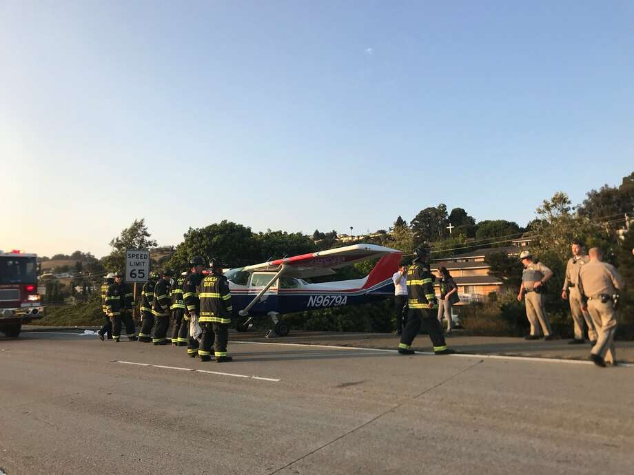 Firefighters and officers investigate a small airplane that landed on I-580 in Hayward on Saturday evening. Photo: Sara Kate Berg