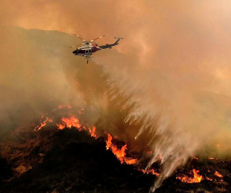 A helicopter drops water to a brush fire at the Holy Fire in Lake Elsinore, California, southeast of Los Angeles, on August 11, 2018. - The fire has burned 21,473 acres and was 29 percent contained as of 8:30 a.m. Saturday, according to the Cleveland National Forest. (Photo by RINGO CHIU / AFP)RINGO CHIU/AFP/Getty Images Photo: RINGO CHIU / AFP or licensors
