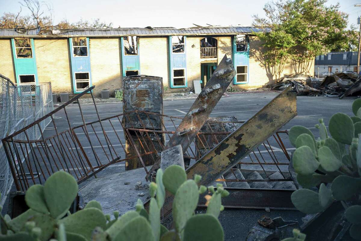 The remains of an outdoor stairwell sit in the parking lot at the Iconic Village Apartments in San Marcos, where a catastrophic fire erupted two hours before dawn on July 20. Building 500, where the fire started and five young adults were found dead, is shown in the background.