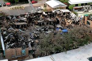 An aerial photograph shows the aftermath of a deadly fire at Iconic Village Apartments in San Marcos. This is Building 500, where the fire started and where five young adults were later found dead. Investigators are considering if a large tree — now blackened and destroyed, and shown toward the right of the courtyard — played any role in the spread of the flames.