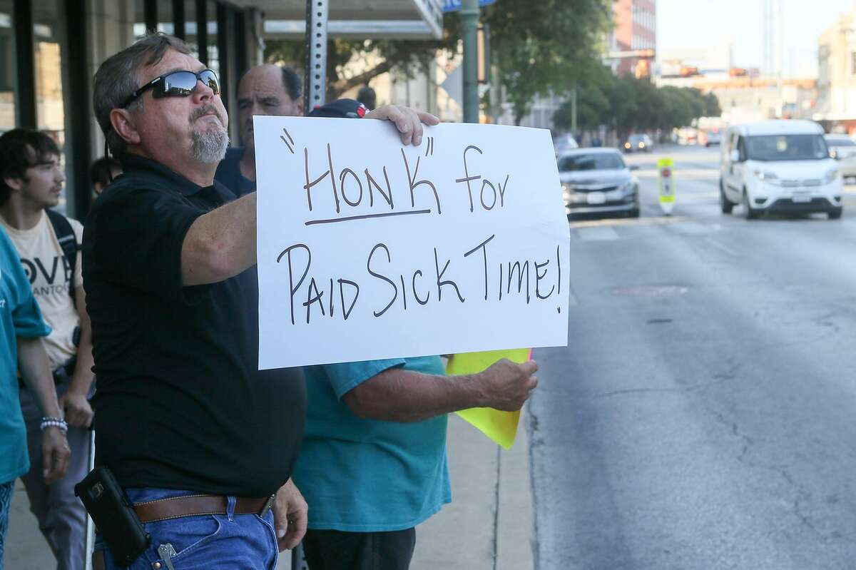 """Rick Sisk holds up a """"Honk for Paid Sick Time!"""" sign to passing cars as members of Working Texans for Paid Sick Time rally in front of City Hall about a proposal for mandatory paid sick leave Aug. 2, 2018."""