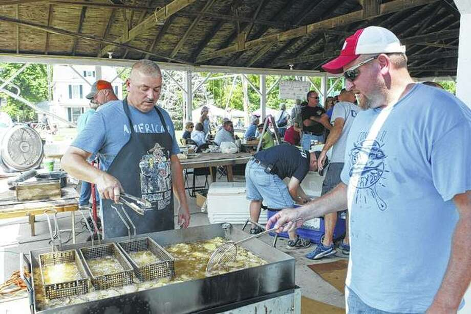 "Arron Lomelino of Jacksonville (left) and George Lomelino of Chapin fry catfish, buffalo and potatoes Saturday at the Concord Fish Fry in Concord Park. The event featured craft and food vendors, games, raffles and musical entertainment. ""Proceeds from the fish fry will go back into future town projects and to fund future fish fries,"" event organizer Katie McDannald of Jacksonville said. Photo:       Greg Olson 