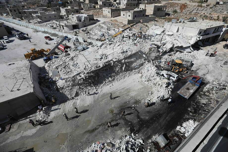 Residents of Sarmada, Syria, examine the site where two five-story buildings collapsed in an explosion. A monitoring group said an arms depot in the basement of a building had detonated. Photo: Omar Haj Kadour / AFP / Getty Images