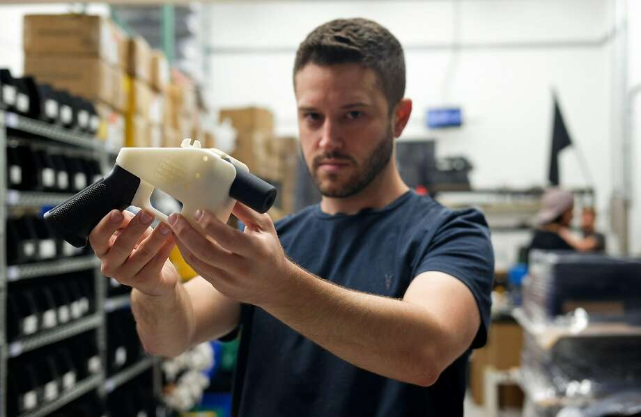 "Cody Wilson, owner of Defense Distributed company, holds a 3D printed gun called the ""Liberator"", in his factory in Austin. A federal judge in Seattle on Monday blocked the Trump administration from allowing the company to post online plans for making untraceable 3D guns. Photo: KELLY WEST, AFP/Getty Images"