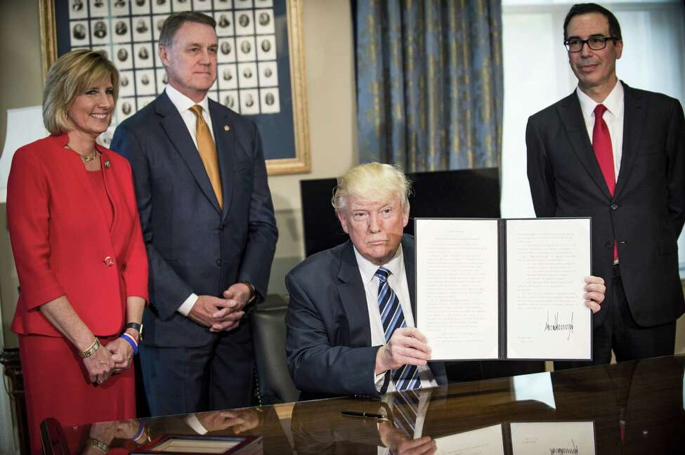 U.S. President Donald Trump, center, displays a signed directive on tax and Wall Street regulations as Steven Mnuchin, U.S. Treasury secretary, right, Representative Claudia Tenney, a Republican from New York, left, and Senator David Perdue, a Republican from Georgia, stand in Washington, D.C., U.S., on Friday, April 21, 2017. The tax code became too expensive and burdensome under former President Barack Obama's administration, making a review of 2016 and 2017 tax rules necessary, Mnuchin said. Photographer: Pete Marovich/Bloomberg ORG XMIT: 700038545