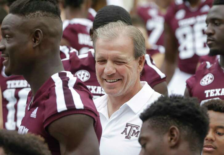 Jimbo Fisher, Texas A&M football coach, is shown with players after a team photo at Kyle Field Sunday, Aug. 12, 2018, in College Station.