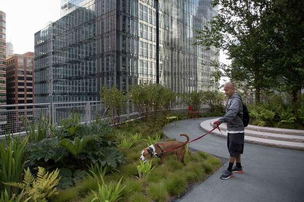 Raul Garcia walks his dog, Lucky, in the transit center's rooftop park.