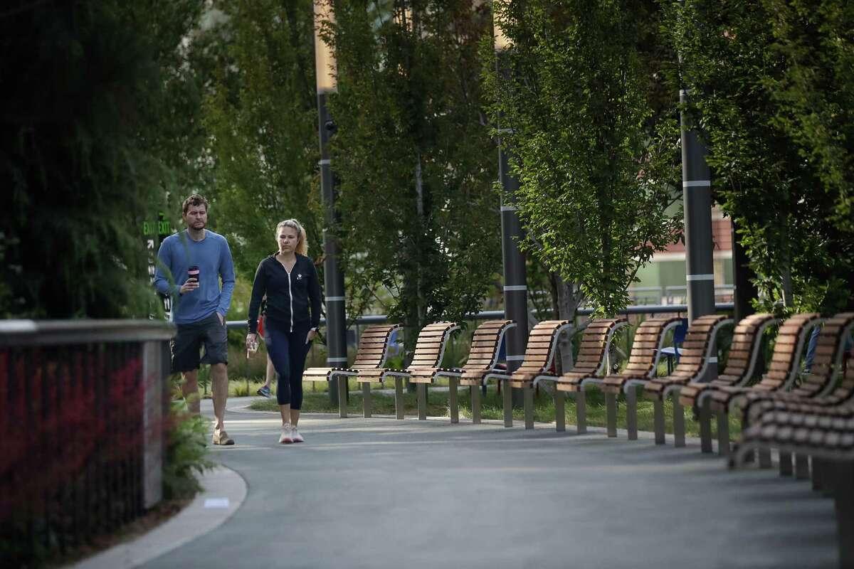 Chris and Amanda Kopel, who live next door, walk at Salesforce Park atop the transit center.
