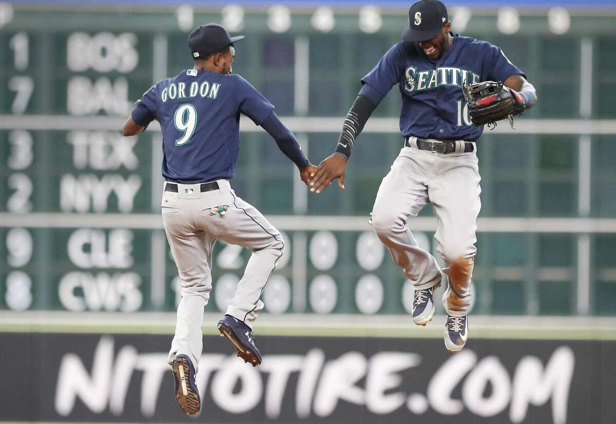 Seattle Mariners second baseman Dee Gordon (9) and Seattle Mariners left fielder Cameron Maybin (10) celebrate a win after an MLB game at Minute Maid Park Sunday, Aug. 12, 2018, in Houston.