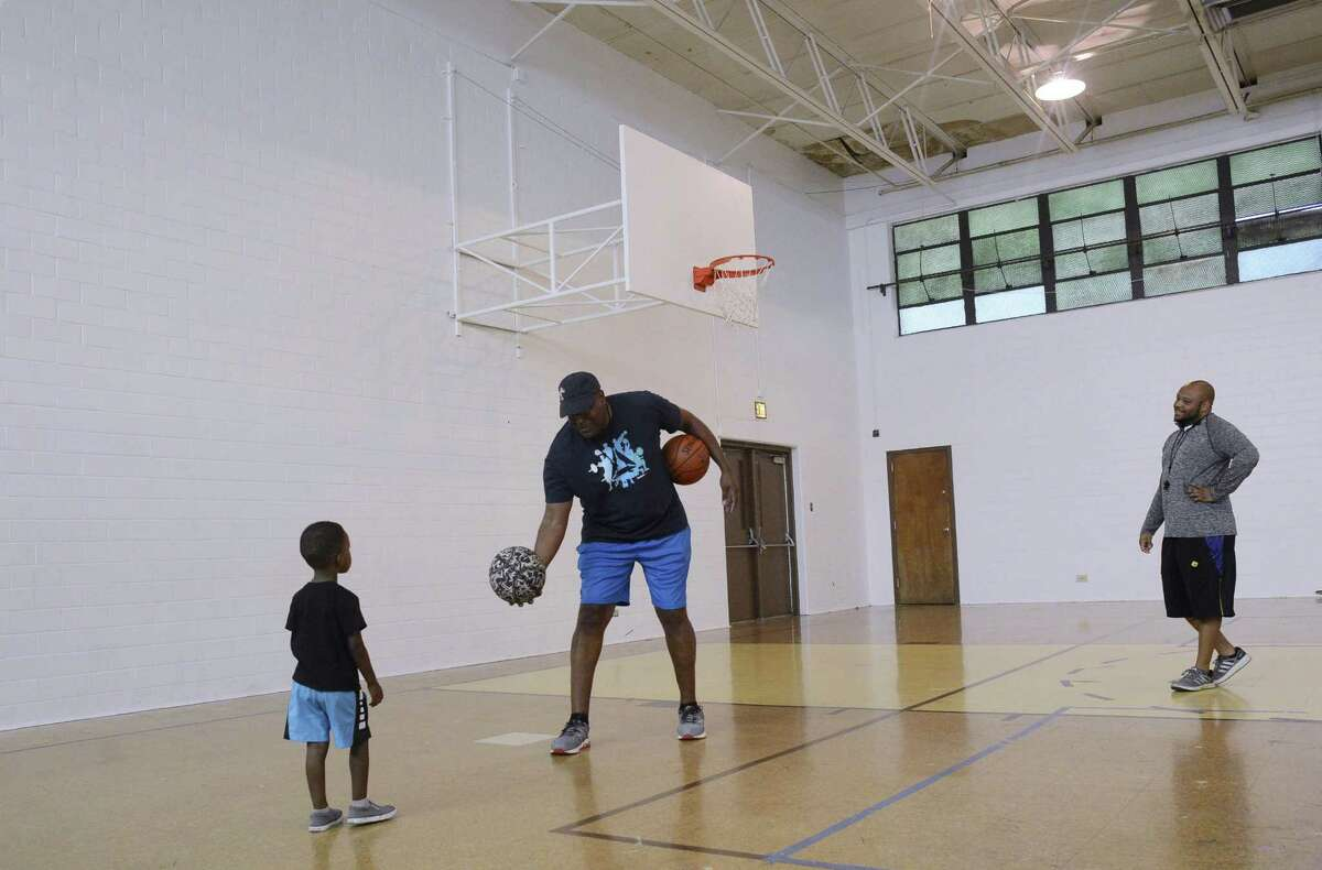 Kelly Moore offers a basketball to a child before a 100 Black Men of San Antonio practice earlier this summer. Fellow coach Darnell Brooks is at right.