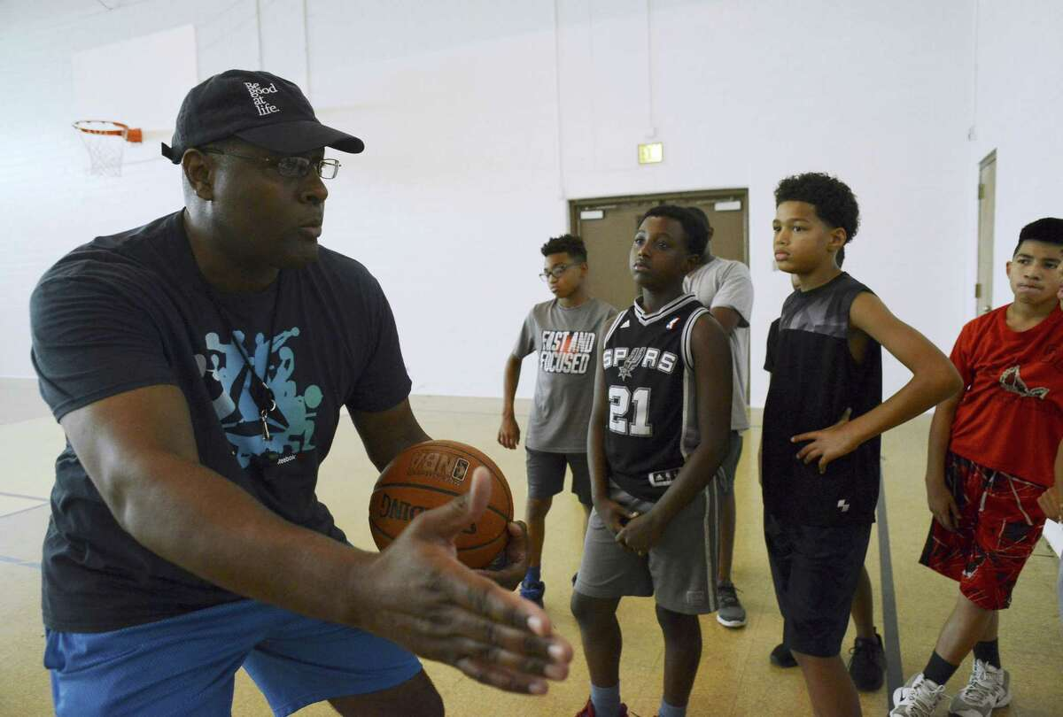 Kelly Moore of 100 Black Men of San Antonio teaches basketball to a group of boys ages 12-17 earlier this summer.