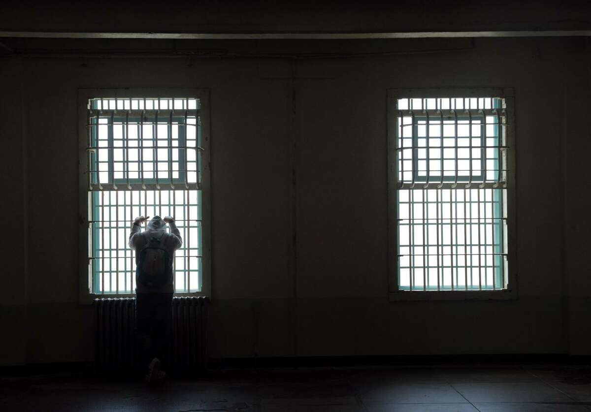 Tourist Murat Poyraz of Germany looks out the window bars while visiting the former prison on Alcatraz.