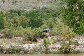 A pickup truck can be seen stranded on an island after heavy rains overnight and Sunday morning, August 12, 2018, caused the Nueces River to swell. Over two dozen people were rescued, according to the Uvalde County Sheriff's Office, and no serious injuries were reported.