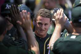 Oakland Athletics' Matt Chapman is congratulated by teammates in the dugout after scoring on a sacrifice fly by Khris Davis during the first inning of a baseball game against the Los Angeles Angels, Sunday, Aug. 12, 2018, in Anaheim, Calif. (AP Photo/Mark J. Terrill)