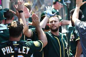 ANAHEIM, CA - AUGUST 12:  Jed Lowrie #8 of the Oakland Athletics is congratulated in the dugout after hitting a three run home run in the fourth inning of the game against the Los Angeles Angels of Anaheim at Angel Stadium on August 12, 2018 in Anaheim, California.  (Photo by Jayne Kamin-Oncea/Getty Images)