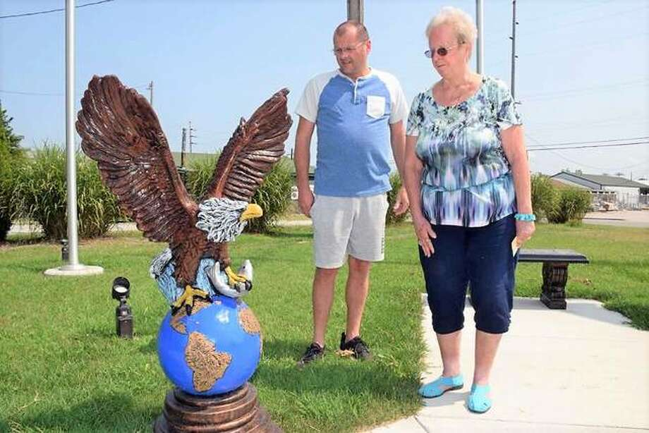 Jason Bricker and Charlotte Wiegand examine the eagle sculpture at the East Alton American Legion Veterans Memorial Park. A monument listing all East Alton residents killed in action during the nation's wars will soon be installed at the site. Photo:     David Blanchette | For The Telegraph