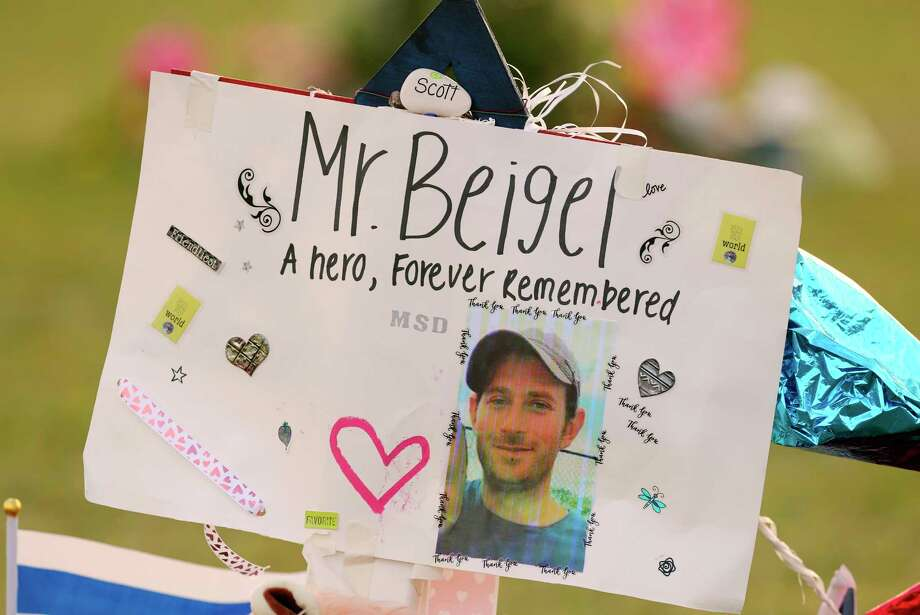"FILE - This Feb. 20, 2018, file photo shows a memorial for Geography teacher and cross-country coach, Scott Beigel at Pine Trails Park in Parkland, Fla. A street in New York's Long Island has been named for Beigel who helped shield students from the gunman in last winter's school shooting. The street where Beigel grew up in Dix Hills, N.Y., was dedicated ""Scott J. Beigel Way"" on Saturday Aug. 11. (Mike Stocker/South Florida Sun-Sentinel via AP, File) Photo: Mike Stocker / Sun Sentinel 2018"