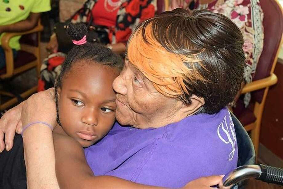 Clearther White hugs her great-great-great-granddaughter, five-year-old Dezira'e Thompson, during White's 100th birthday party on Sunday. Photo:     David Blanchette | For The Telegraph